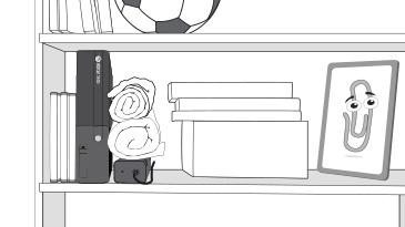 Una consola Xbox 360 está sobre un estante, sin mucho espacio entre varias cajas de juegos y ropa enrollada, encima de la fuente de alimentación.