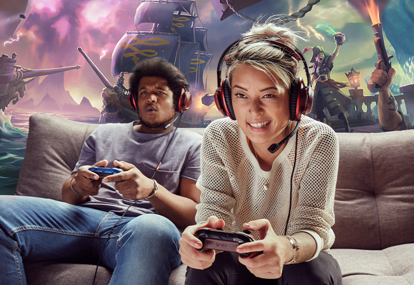 Two people wearing headsets playing Xbox games on a couch together