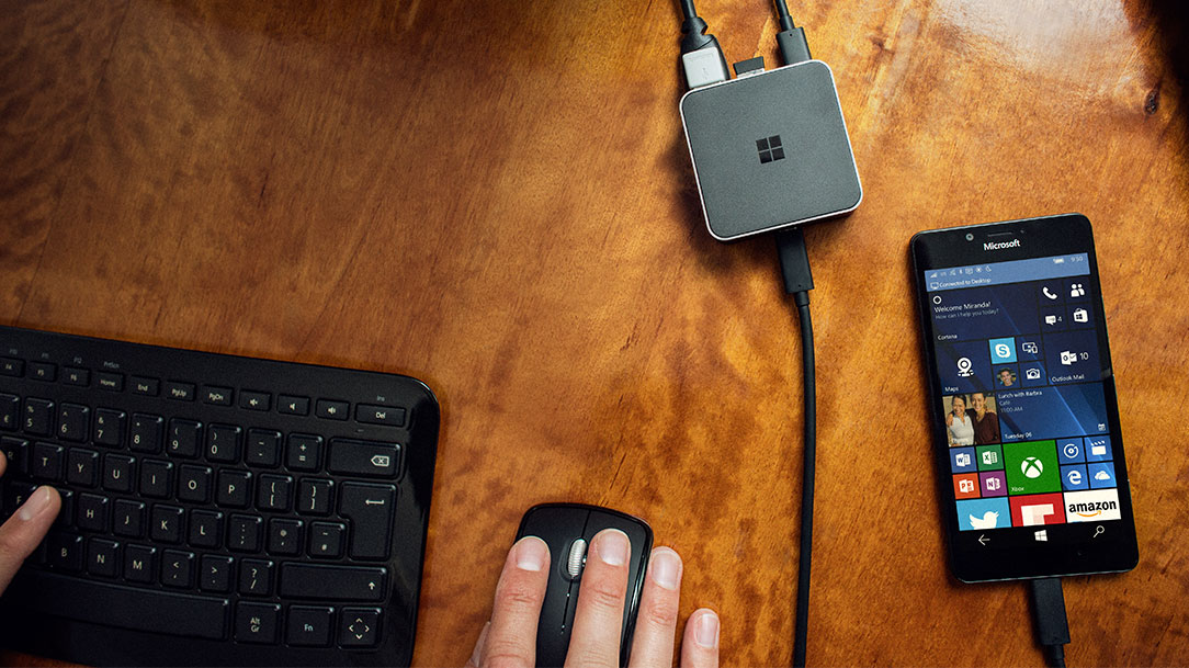 Man's hands on a mouse and keyboard, with a Lumia 950 plugged into a Microsoft Display dock next to him on the desk