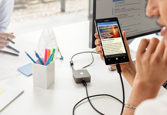 Woman holding a Lumia 950 XL plugged into a Microsoft display dock, talking to a male colleague across a table wit ha monitor  and keyboard on it.