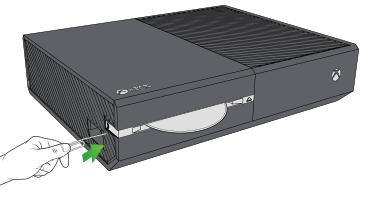 На рисунке показана рука, которая вставляет прямой конец распрямленной скрепки для бумаги в отверстие для выталкивания на стенке консоли Xbox One