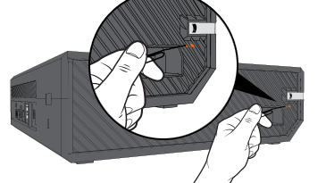 An illustration of a hand holding an uncoiled large paper clip, with the straight end of the paper clip pointing toward the small orange rectangle behind the vents on the left side of an Xbox One console