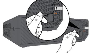 Una ilustración de una mano sujetando un clip grande desenrollado, con el extremo recto apuntando hacia el pequeño rectángulo naranja situado detrás de la rejilla del lateral izquierdo de una consola Xbox One